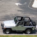 A parked Jeep Wrangler Unlimited with the soft top down.