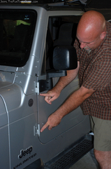 Pointing to the 2 door hinges on the Jeep Wrangler door.