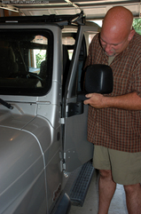 Jim trying to singlehandedly put the Jeep door back on. It's tricky to line up the 2 bolts with the 2 hinges yourself.